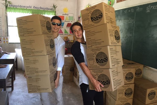 Die Beiden Studenten In Kambodscha Mit Den Boxen, Die Die Filter Enthalten, Um Das Wasser Zu Reinigen